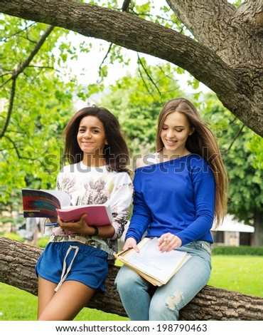 Multi ethnic girls students in a city park  - stock photo