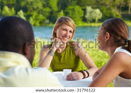 multi ethnic group having picnic outdoors and smiling - stock photo
