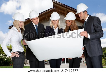 Multi Ethnic Group Of Architects Looking At Blueprint In Front Of Home - stock photo