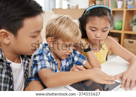 Multi-ethnic group of children drawing on digital tablet - stock photo