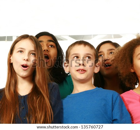 multi-ethnic group of children singing with copy space - stock photo