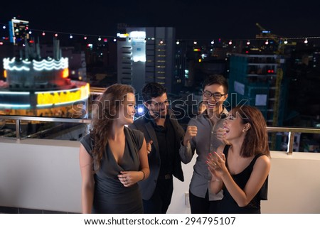 Multi-ethnic group of friends chatting and laughing at the rooftop party - stock photo