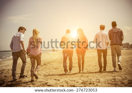 Multi-ethnic group of friends walking on the beach and talking - Group of young adults silhouettes at sunset - stock photo