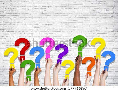 Multi-Ethnic group of human hands holding question marks. - stock photo