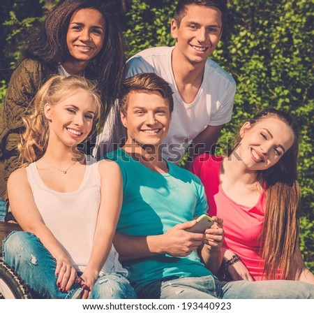 Multi ethnic group of teenage friends in a park  - stock photo