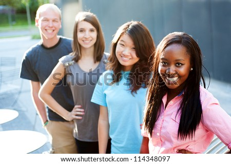 Multi-ethnic group of teenagers outside smiling - stock photo