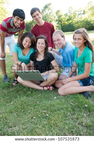Multi-ethnic group of teens outside looking at a computer - stock photo