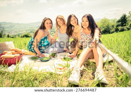 Multi-ethnic group of women enjoying picnic in the countryside and taking a picture with selfie stick - Four girls on vacation having fun - stock photo