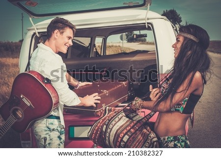 Multi-ethnic hippie couple with guitar packing luggage for a road trip - stock photo