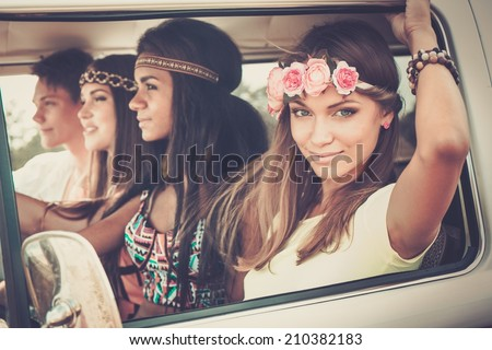 Multi-ethnic hippie friends in a minivan on a road trip - stock photo