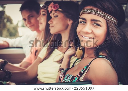 Multi-ethnic hippie friends in a minivan on a road trip - stock photo