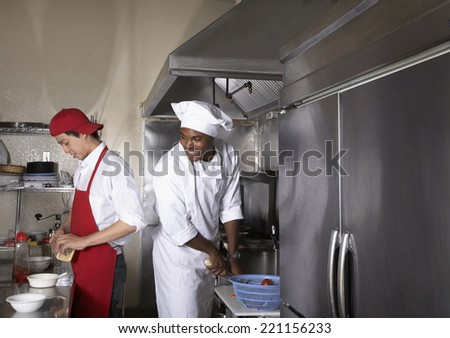 Multi-ethnic male chefs preparing food - stock photo