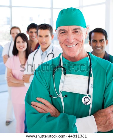 Multi-ethnic medical group smiling at the camera in a hospital - stock photo