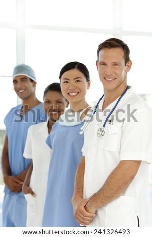Multi-ethnic Medical staff standing in a row at the hospital - portrait - stock photo