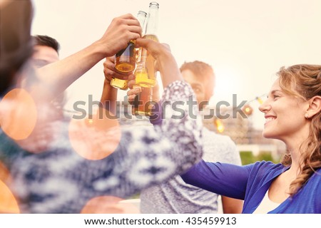 Multi-ethnic millenial group of friends partying and enjoying a beer on rooftop terrasse at sunset - stock photo