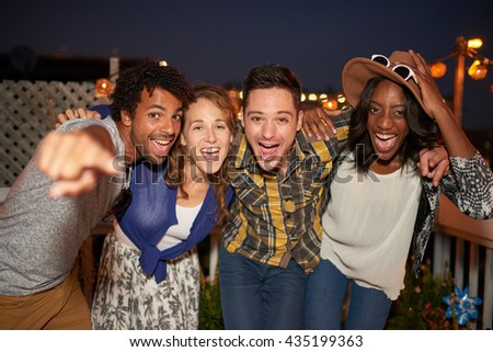 Multi-ethnic millenial group of friends taking a flash selfie photo with mobile phone on rooftop terrasse at night time - stock photo