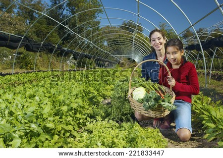 Multi-ethnic mother and daughter harvesting organic produce - stock photo