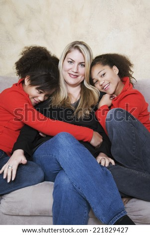 Multi-ethnic mother and twin daughters hugging - stock photo