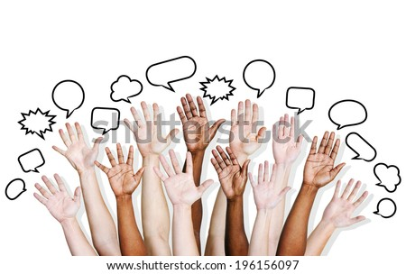 Multi ethnic people's hands raised with speech bubble. - stock photo