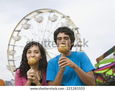 Multi-ethnic teenaged couple eating candied apples - stock photo