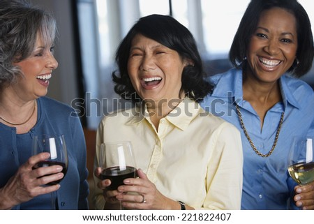 Multi-ethnic women drinking wine - stock photo
