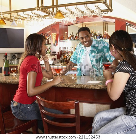 Multi-ethnic women sitting at bar - stock photo