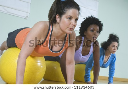 Multi ethnic women using exercise balls in fitness class - stock photo