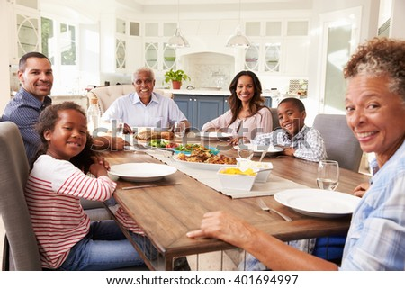 Multi generation black family at kitchen table for a meal - stock photo