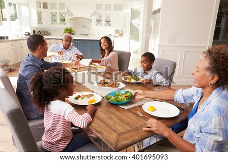 Multi generation black family serving a meal in the kitchen - stock photo