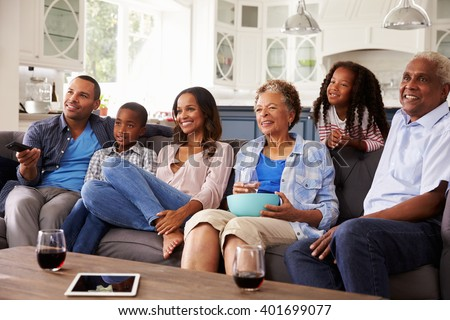 Multi generation black family watching movie on TV together - stock photo
