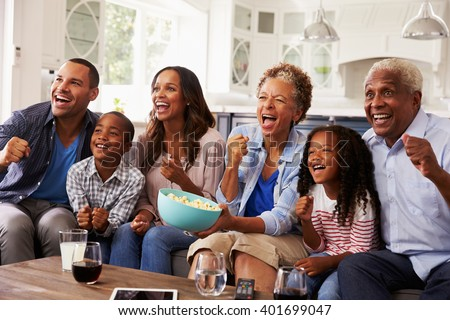 Multi generation black family watching sport on TV at home - stock photo