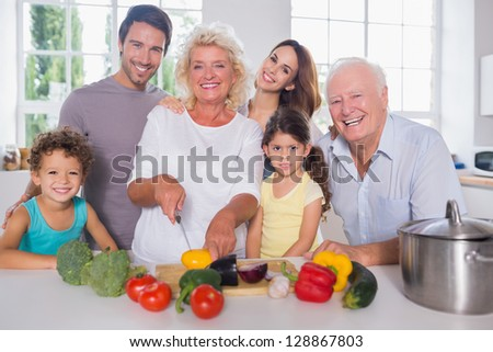 Multi-generation family cutting vegetables together in the kitchen - stock photo