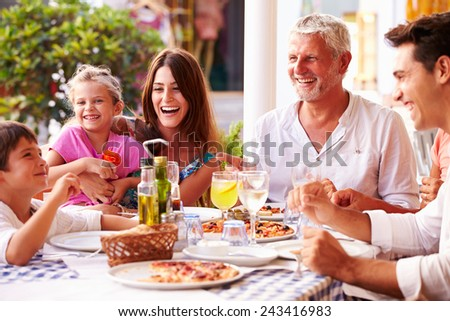 Multi Generation Family Eating Meal At Outdoor Restaurant - stock photo