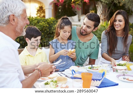 Multi Generation Family Eating Meal At Outdoors Together - stock photo