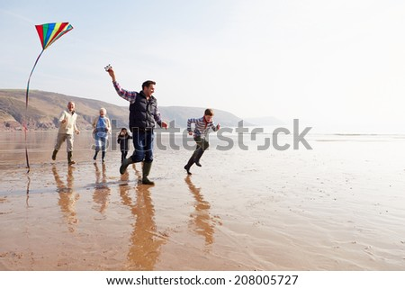 Multi Generation Family Flying Kite On Winter Beach - stock photo