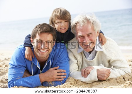 Multi Generation Family Lying On Beach Together - stock photo