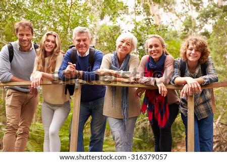 Multi-generation family on a bridge in forest, portrait - stock photo