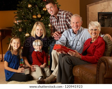 Multi Generation Family Opening Christmas Presents In Front Of Tree - stock photo
