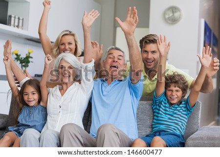 Multi-generation family raising their arms together in the living room - stock photo