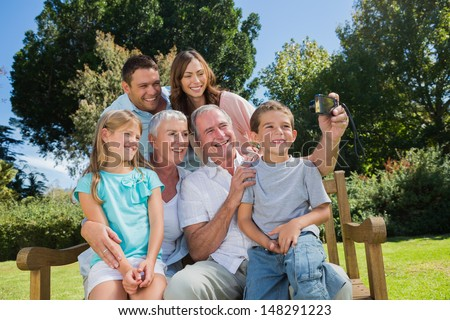 Multi generation family sitting on a bench taking photo of themselves - stock photo