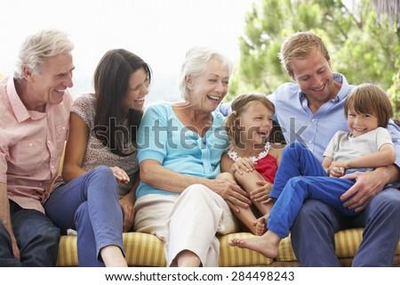 Multi Generation Family Sitting On Garden Seat - stock photo