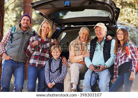 Multi generation family standing by a car before forest hike - stock photo