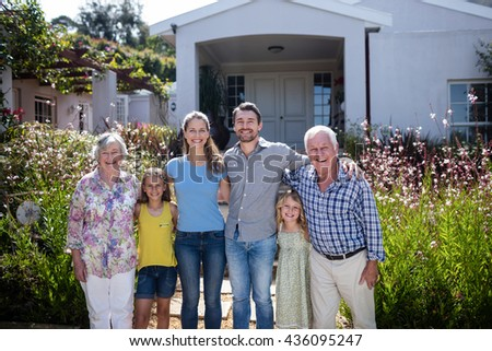Multi-generation family standing together on the garden path - stock photo