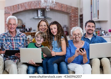 Multi-generation family using a laptop, tablet and phone at home - stock photo