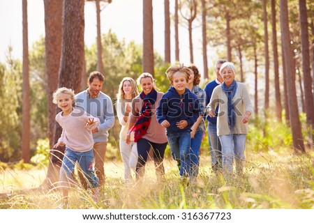 Multi-generation family walking in countryside, kids running - stock photo