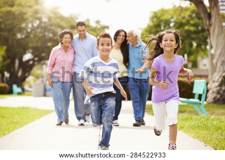 Multi Generation Family Walking In Park Together - stock photo