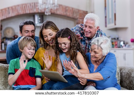 Multi-generation family waving hands while using digital tablet for video chat at home - stock photo