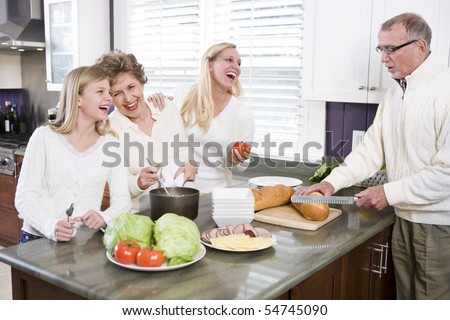 Multi-generational family making lunch in kitchen, laughing and talking - stock photo