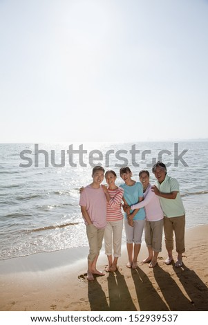 Multi generational family portrait, arms around each other by the beach - stock photo