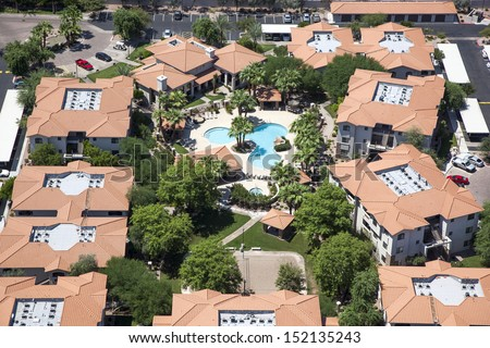 Multi level apartment living with swimming pool and volleyball as viewed from above - stock photo
